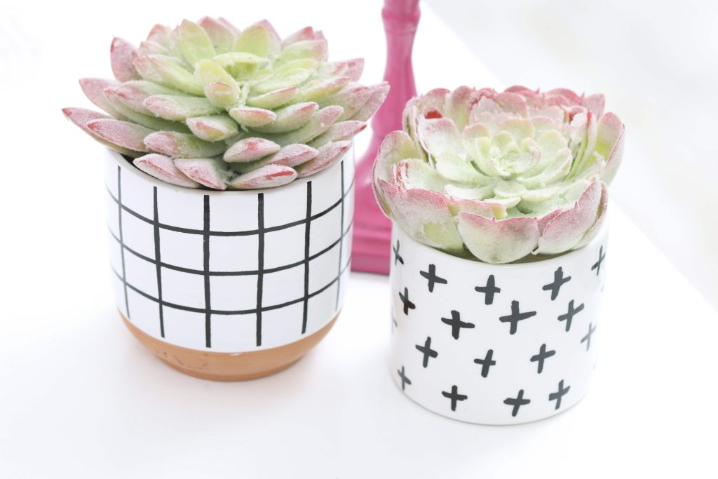 pink taper candle and modern black and white succulent table decor