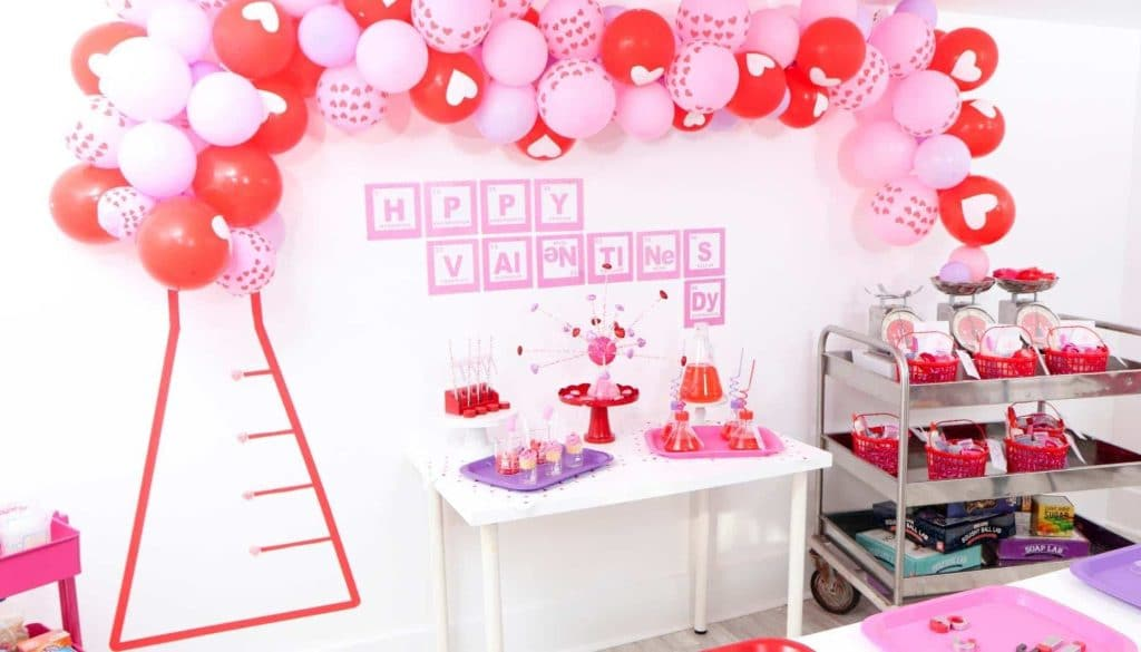 "Create a ""Laboratory of Love"" DIY Backdrop for kids who love to learn this Valentine's Day! Get all of the details for a pink and red Valentine's Day Science Party for kids now at fernandmaple.com!"
