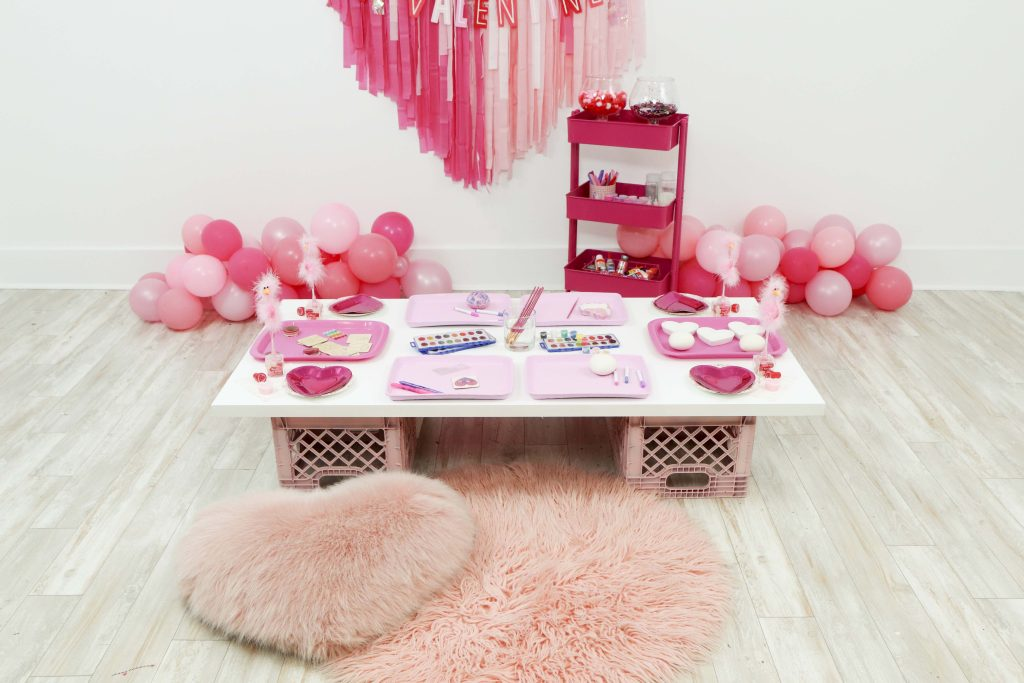 Valentine's craft table for a Valentine's Day Craft Party for Kids with fringe heart backdrop, craft cart, and craft table ideas! Get all of the details now at fernandmaple.com!