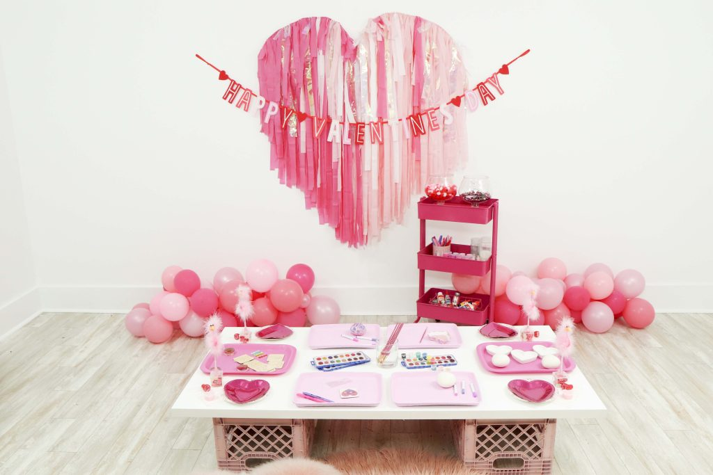 Throw a Valentine's Day Craft Party for Kids with fringe heart backdrop, craft cart, and craft table ideas! Get all of the details now at fernandmaple.com!