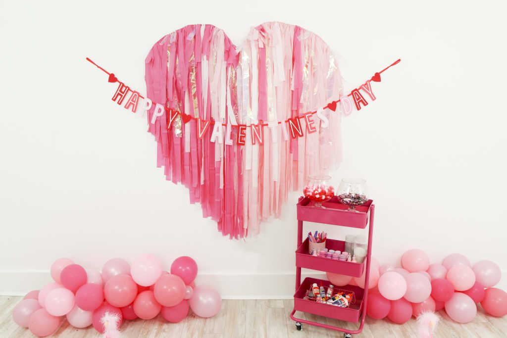 Valentine's backdrop and garland for a Valentine's Day Craft Party for Kids with fringe heart backdrop, craft cart, and craft table ideas! Get all of the details now at fernandmaple.com!