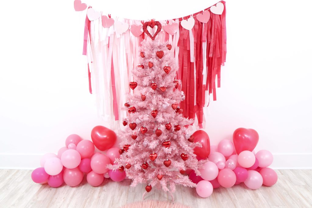 Valentine's Day pink tree- decorate a Valentine's Day tree at a tree decorating party with fun backdrop, decor, and candy heart ornament craft! Get details now at fernandmaple.com.