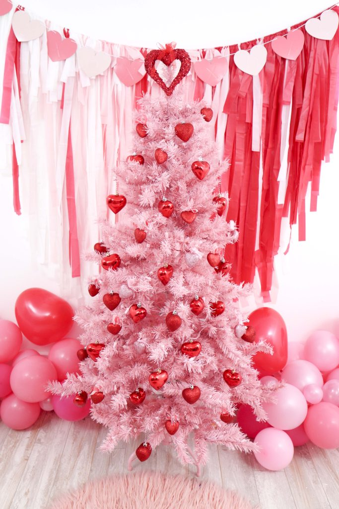 Valentine's Day pink decorated tree- decorate a Valentine's Day tree at a tree decorating party with fun backdrop, decor, and candy heart ornament craft! Get details now at fernandmaple.com.