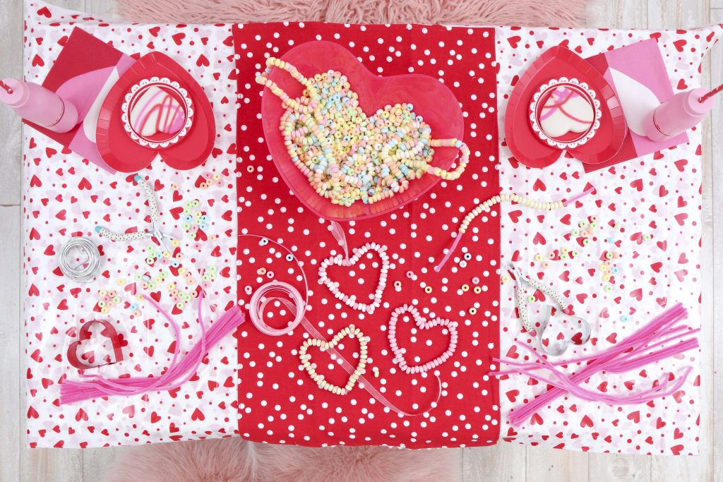 Craft table setup - decorate a Valentine's Day tree at a tree decorating party with fun backdrop, decor, and candy heart ornament craft! Get details now at fernandmaple.com.