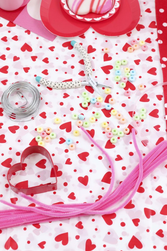 Valentine's Day craft station- decorate a Valentine's Day tree at a tree decorating party with fun backdrop, decor, and candy heart ornament craft! Get details now at fernandmaple.com.
