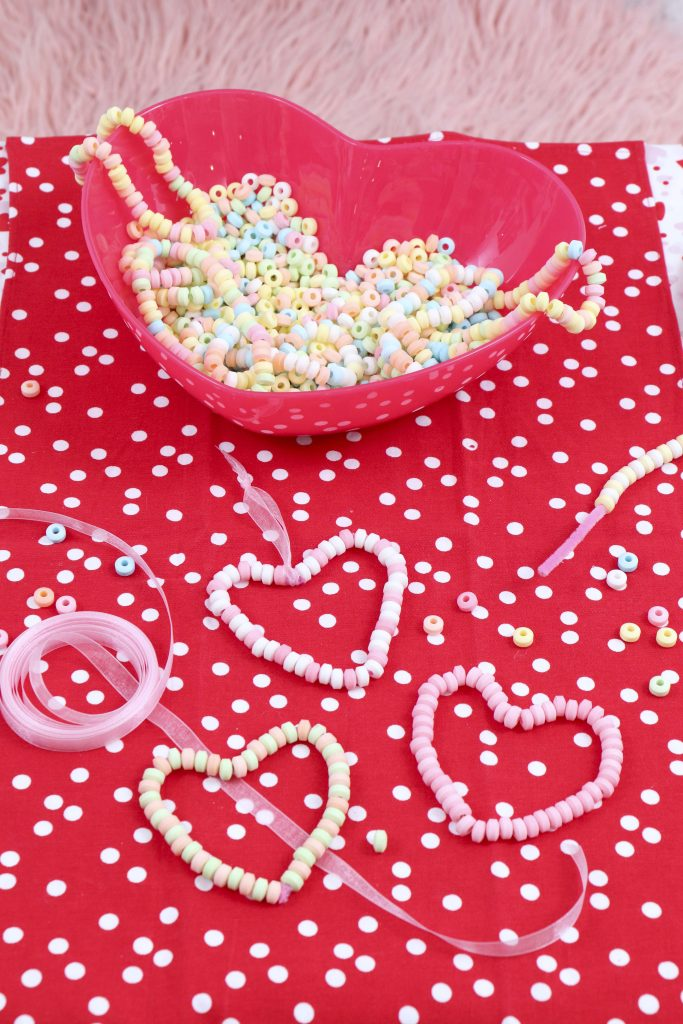 Valentine's Day Candy Heart Ornament station- decorate a Valentine's Day tree at a tree decorating party with fun backdrop, decor, and candy heart ornament craft! Get details now at fernandmaple.com.