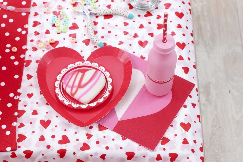 Valentine's Day kid's party place setting - decorate a Valentine's Day tree at a tree decorating party with fun backdrop, decor, and candy heart ornament craft! Get details now at fernandmaple.com.