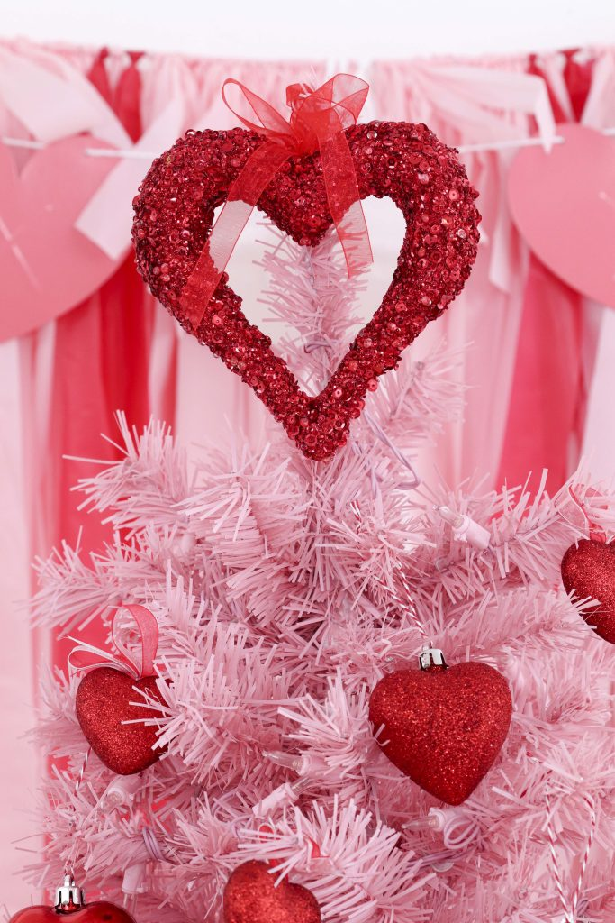 Valentine's Day tree topper- decorate a Valentine's Day tree at a tree decorating party with fun backdrop, decor, and candy heart ornament craft! Get details now at fernandmaple.com.