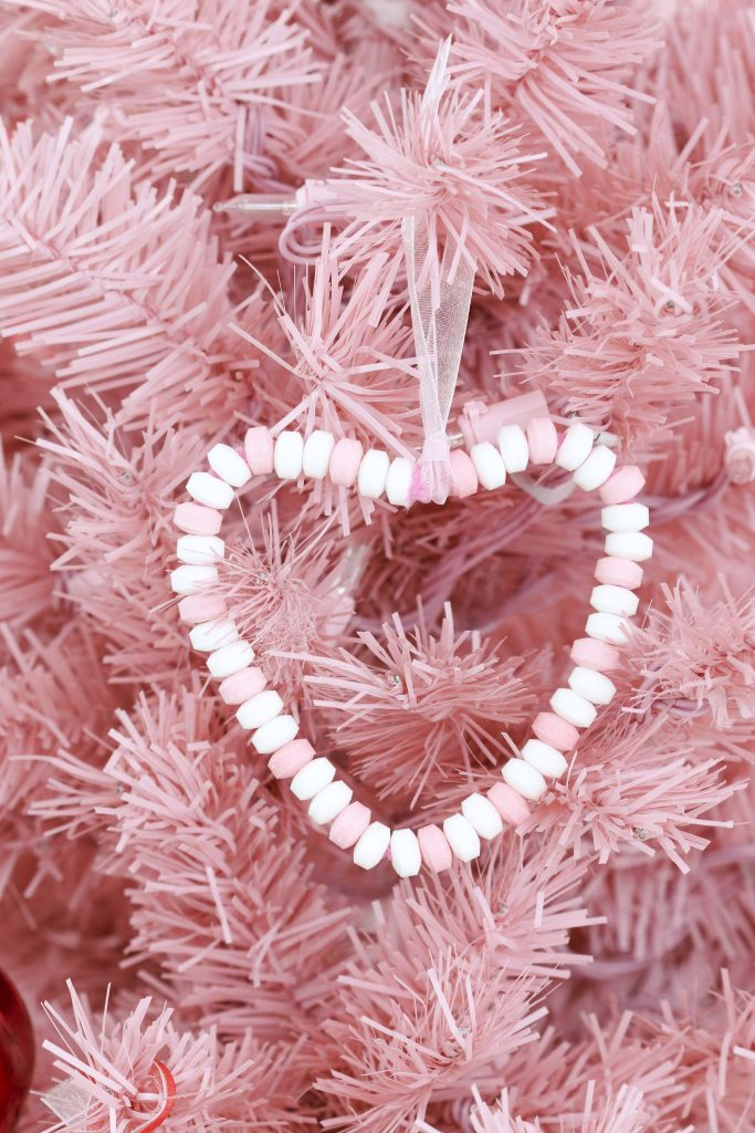 Valentine's Day Candy Heart Ornament craft- decorate a Valentine's Day tree at a tree decorating party with fun backdrop, decor, and candy heart ornament craft! Get details now at fernandmaple.com.