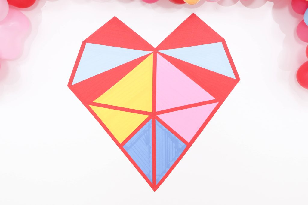 Colorful and modern Geometric Heart Valentine's Day Party DIY backdrop - Get details and more party ideas now at fernandmaple.com!