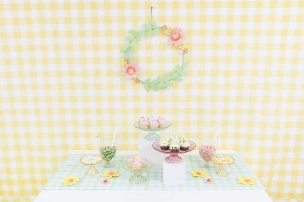 Spring Dessert Table with yellow gingham backdrop and felt floral wreath - get more Spring Party inspiration now at fernandmaple.com!