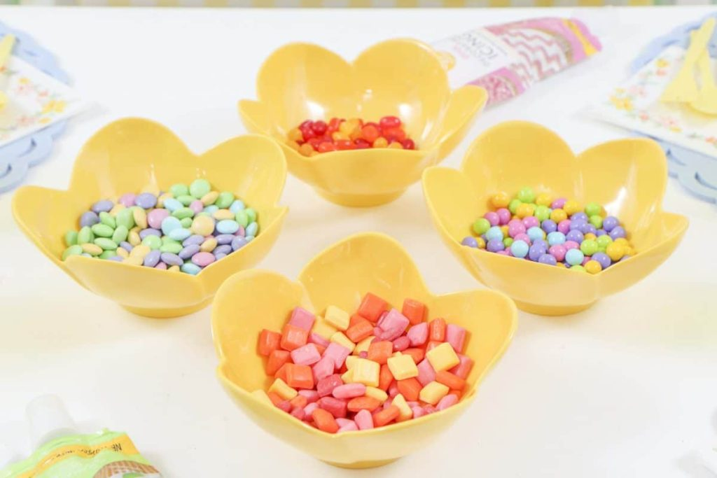Candies in pastel yellow flower bowls for a Spring Gingerbread House decorating party - get more Spring Party inspiration now at fernandmaple.com!